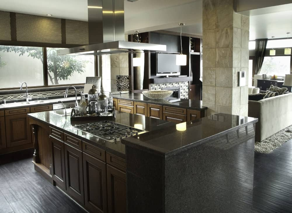 This kitchen offers black kitchen counters and wooden cabinetry, along with hardwood flooring.