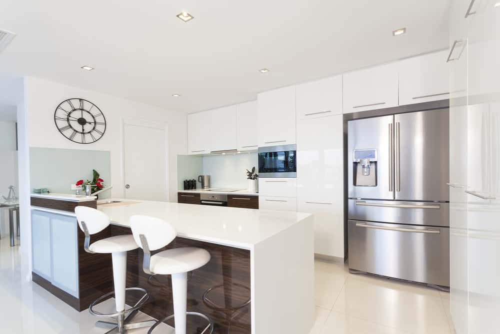 White kitchen featuring large tiles flooring and a white ceiling. It also features a white breakfast bar with a waterfall-style countertop and has modern bar stools.