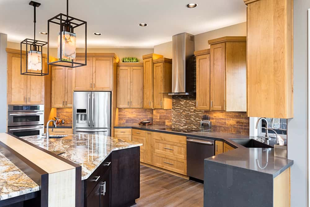 This kitchen features brown cabinetry and gray kitchen counter, along with island both boasting marble countertops.