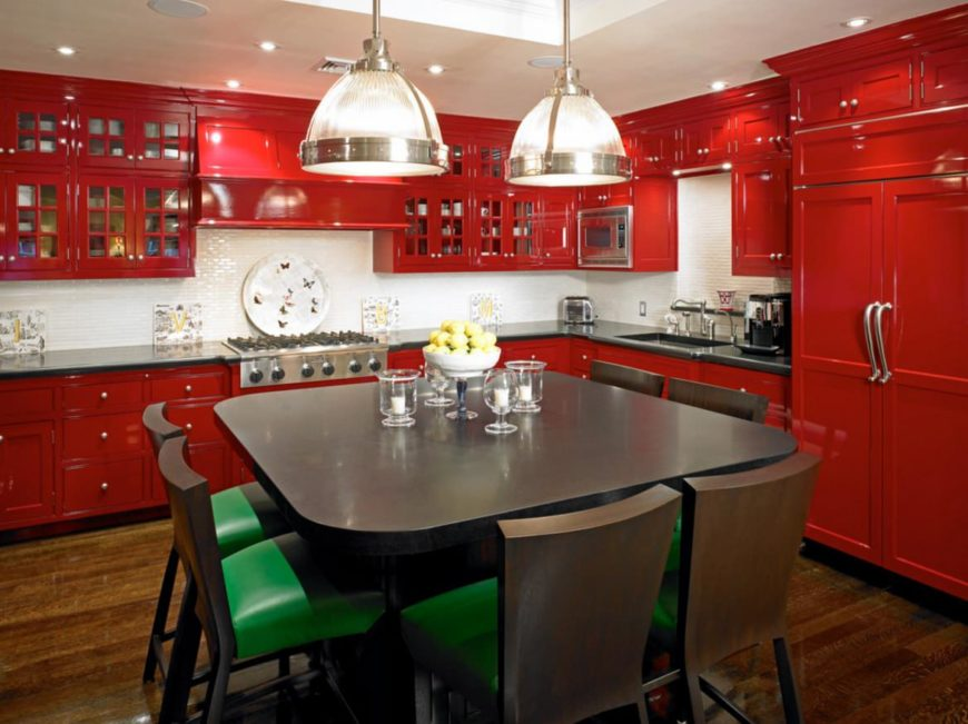 This kitchen boasts red cabinetry and kitchen counters, along with a square dining table set lighted by large pendant lights.