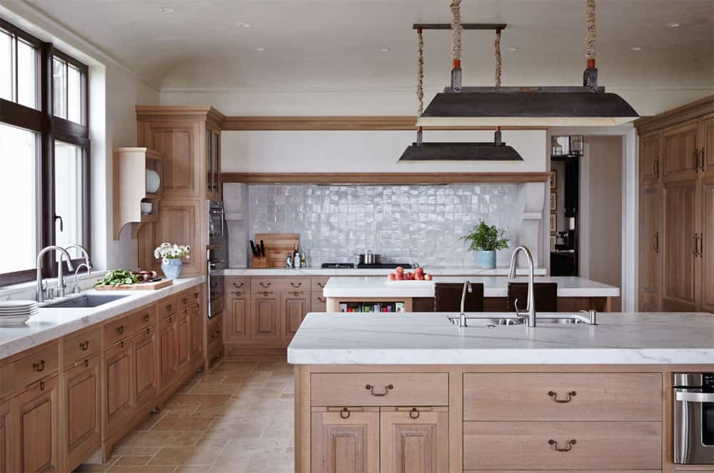 This kitchen features brown cabinetry and kitchen counters, along with two islands, both boasting white marble countertops.
