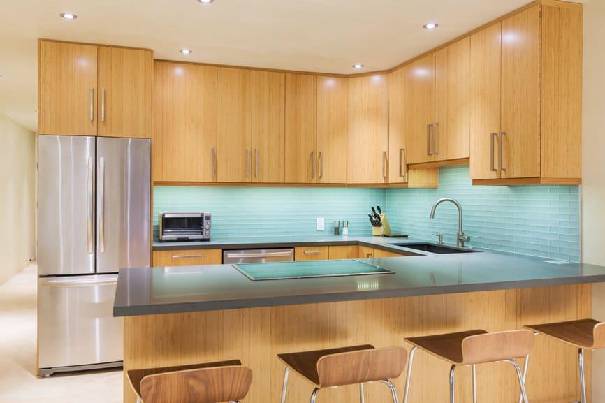 Interesting kitchen with blue glass tile backsplash.