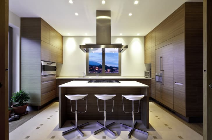 Modern kitchen with dark flat panel cabinets and modern white and chrome bar stools.