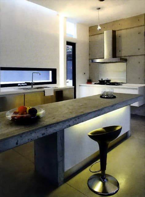 Modern kitchen with concrete island and concrete wall and concrete countertops.