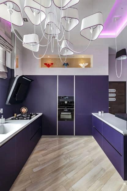 This beautiful and modern purple kitchen has light hardwood flooring and a white ceiling that functions with the white countertops of the peninsulas. They all serve to brighten the deep purple cabinetry with modern drawers and cabinets.