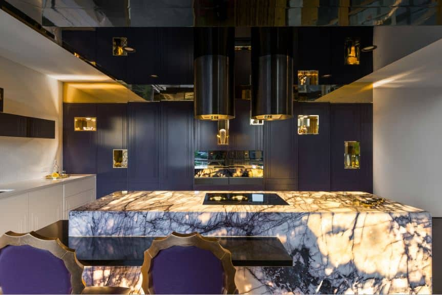 This eclectic and modern kitchen has a waterfall kitchen island made of white and purple marble that sets an amazing foreground for the rest of the kitchen that has dark purple cabinetry complemented by the slick black ceiling panels.