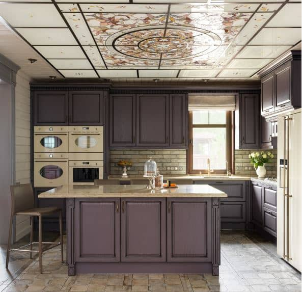 This kitchen has a homey quality to it that is augmented by the natural lights coming in from the window and lightens the deep purple traditional shaker cabinets and drawers. This is then complemented by the beautiful decorative panel on the ceiling that has a painting on it.