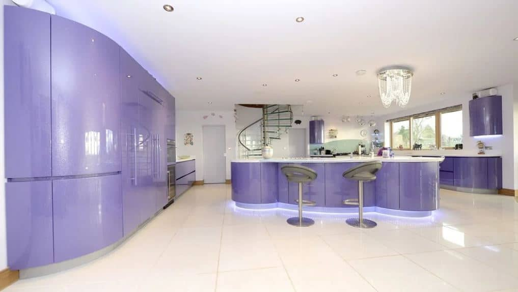 The sleek purple elements of this modern kitchen has a curved design to it that veers away from the traditional lines and edges. This is augmented by the lights underneath the structures that casts blue lights onto the white flooring surrounding the kitchen island.