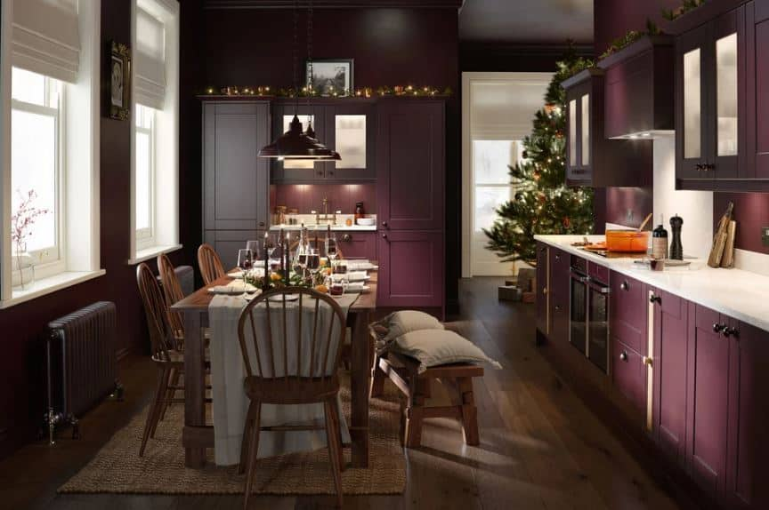 This charming and homey purple kitchen has an informal dining area on its hardwood flooring that is topped with a rustic woven area rug and a farmhouse-style wooden dining set. This works well with the traditional purple shaker cabinets and drawers.