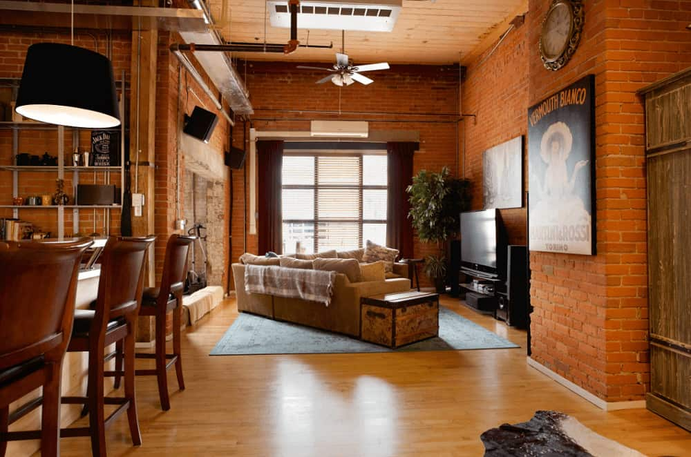 Industrial living area showcases a flat-screen TV and beige velvet sofa with a storage box on the side over the area rug, It is surrounded with red brick walls mounted with lovely artworks and ornate round clock.