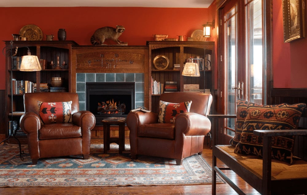 A pair of brown leather armchairs sit in front of the fireplace flanked by wooden shelvings. It has wrought iron floor lamps and a vintage rug that lays on the hardwood flooring.