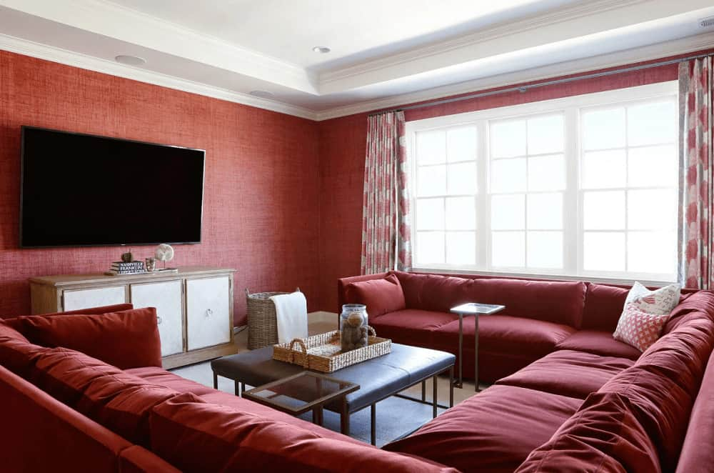 Natural light flows in through the white framed windows in this red living room with a sectional sofa and a leather coffee table topped with a wicker tray. It includes a wall mount TV that hung above the wooden stand.