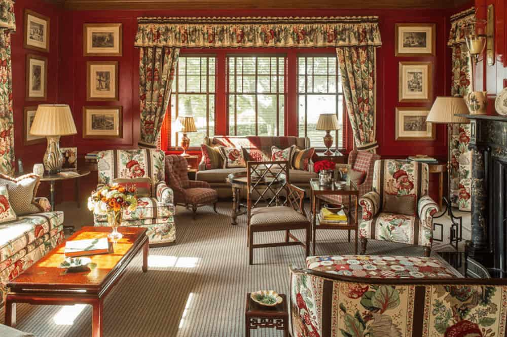 Floral draperies and valances complement the armchairs over a striped area rug. This room has wooden framed windows and red wainscoted walls filled with black and white photos.