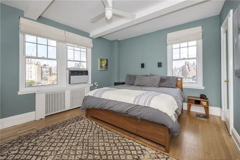 Soft turquoise bedroom made sophisticated with wood parquet flooring and double-hung windows.