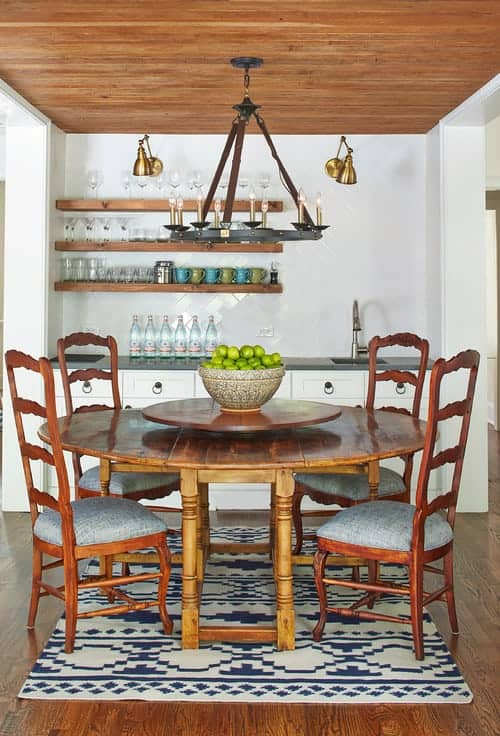 Wooden floating shelves complement the round dining table accompanied by cushioned chairs that sit on a patterned area rug. It blends in with the hardwood flooring and wood paneled ceiling mounted with a wrought iron chandelier.