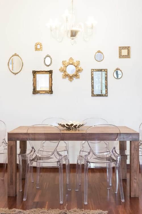 This dining room is decorated with a fancy chandelier and various styled mirrors mounted on the white wall. It has glass chairs and a wooden dining table topped with a decorative bowl.