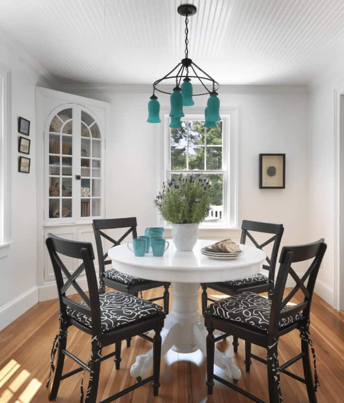 A wrought iron chandelier hangs over the white dining table contrasted by black cushioned chairs. It is accompanied by framed wall arts and a corner cabinet enclosed in an arched door.