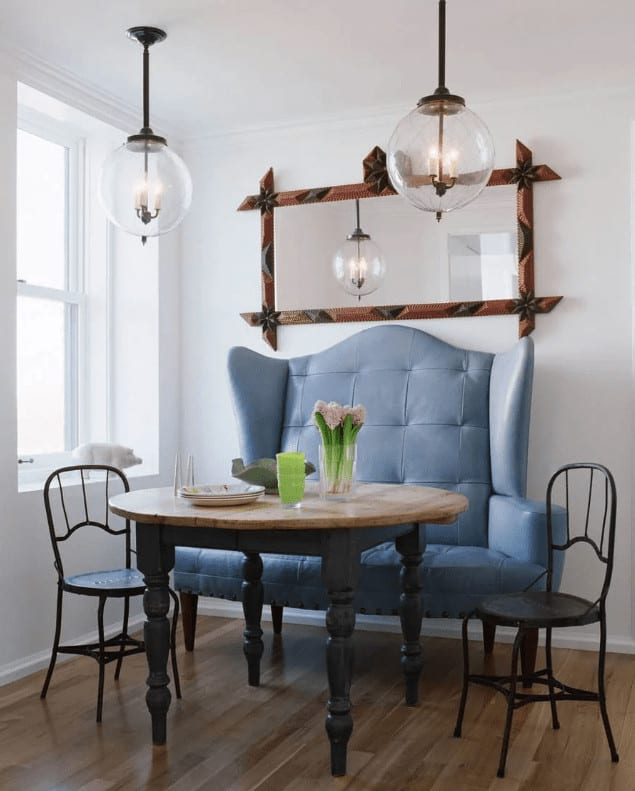 A blue wingback seat stands out against the white walls mounted with a framed mirror. This room offers a round dining table and black metal chairs lighted by glass globe pendants.