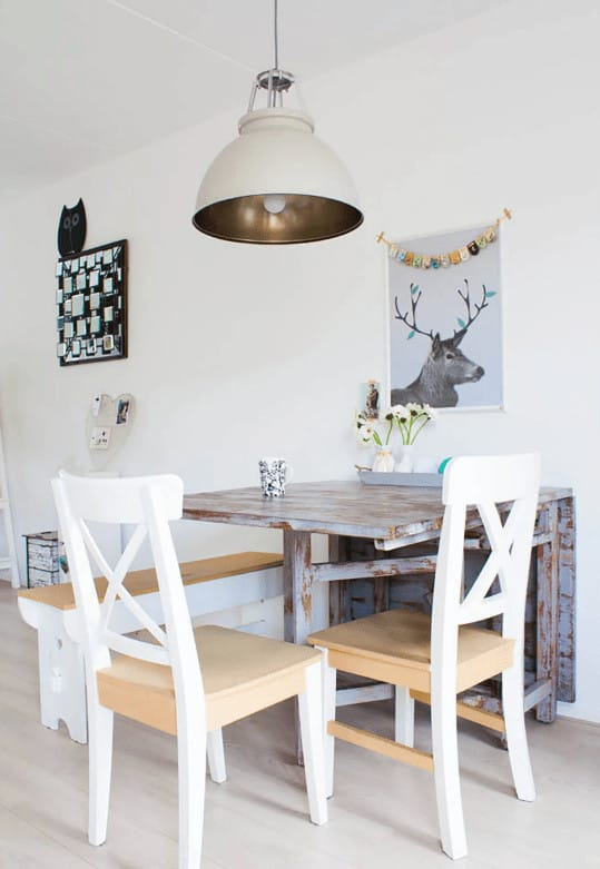 Lovely deer artwork hangs above the blue distressed dining table lighted by a large dome pendant. It is accompanied by wooden bench and chairs over wide plank flooring.