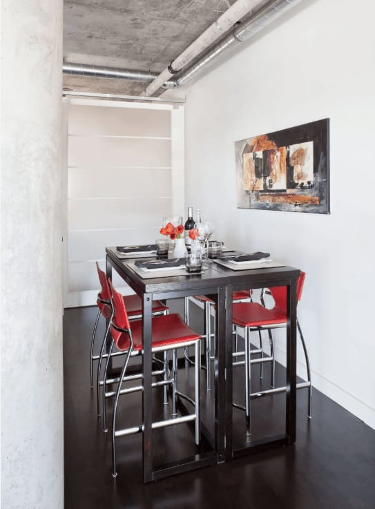 Industrial dining room boasts a metal dining table and red chairs that stand out against the white walls. It has dark hardwood flooring and concrete ceiling lined with exposed pipes.
