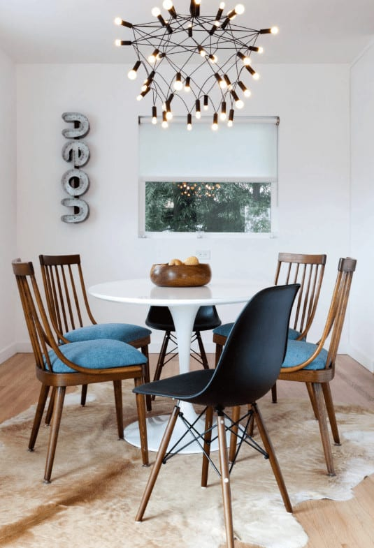 A unique bulb chandelier adds character in this dining room with a round dining table and blue cushioned chairs that sit on a cowhide rug over the light hardwood flooring.