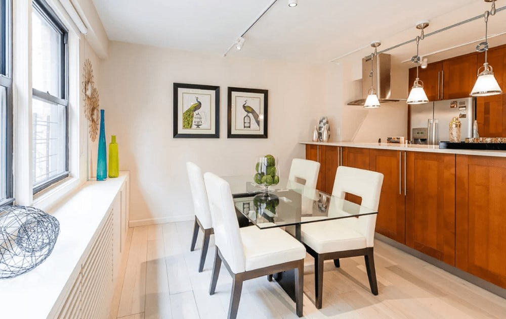Small dining area with modern furniture and gorgeous peacock artworks mounted on the white wall. There's a bar on the side illuminated by glass dome pendant lights.