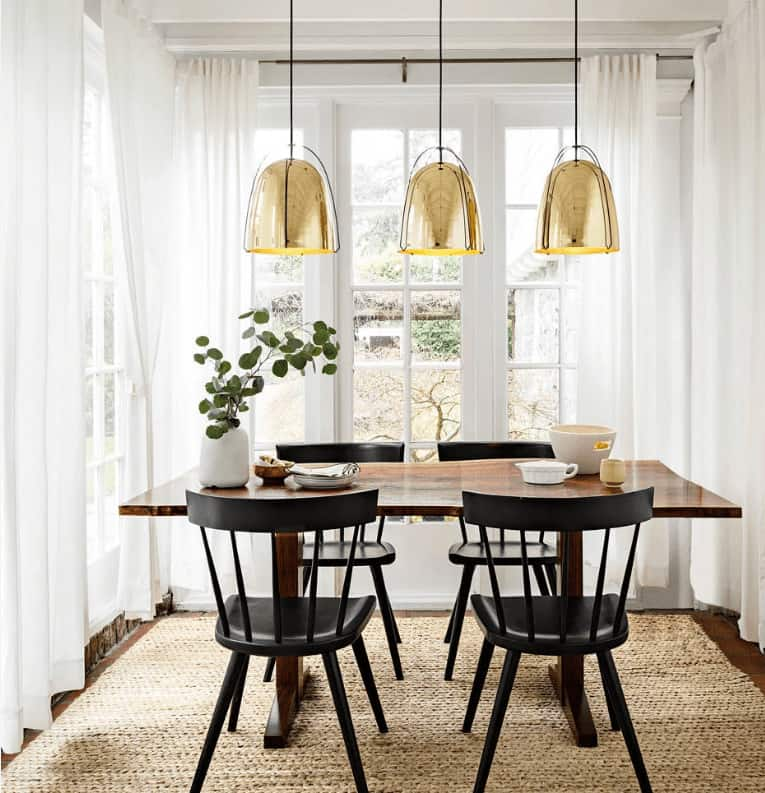 Brass dome pendants hang over the wooden dining table that sits on a jute rug over the dark hardwood flooring. It is accompanied by black chairs that are contrasted with white framed windows covered in sheer curtains.