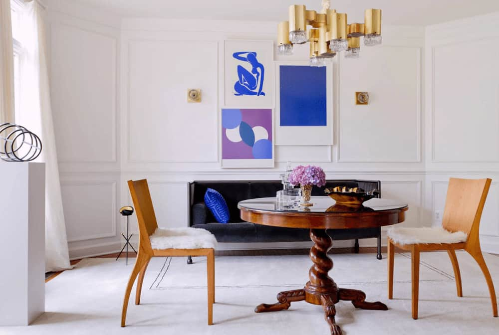Contemporary dining room decorated with a gorgeous brass chandelier and blue artworks mounted on the white wainscoted wall. It has a round dining table surrounded by a black velvet bench and wooden chairs topped with faux fur cushions.