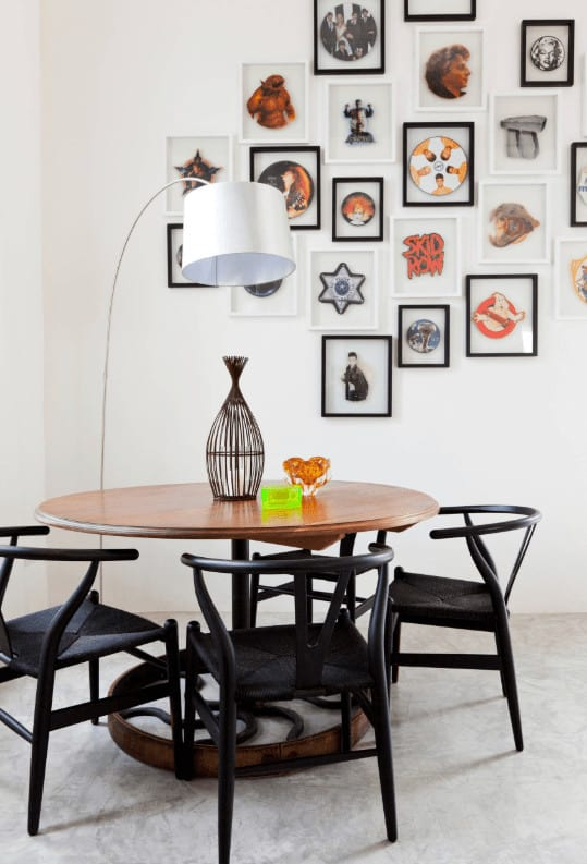 An eclectic art gallery sets a nice backdrop to the black chairs and round dining table topped with various decors. It is illuminated by an arched floor lamp with gray drum shade.