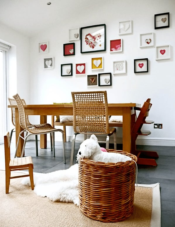 White dining room designed with a heart gallery that's mounted above the wooden bench. It has a rectangular dining table and mismatched chairs along with a rattan bin that sits on a jute bordered rug.