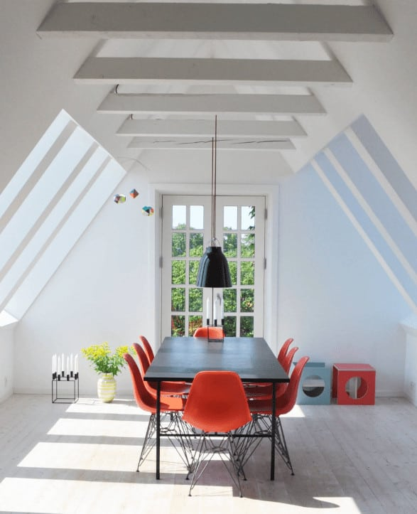 Red modern chairs add a striking contrast to the black dining table illuminated by a dome pendant light. This room has a French door and a cathedral ceiling lined with white beams.