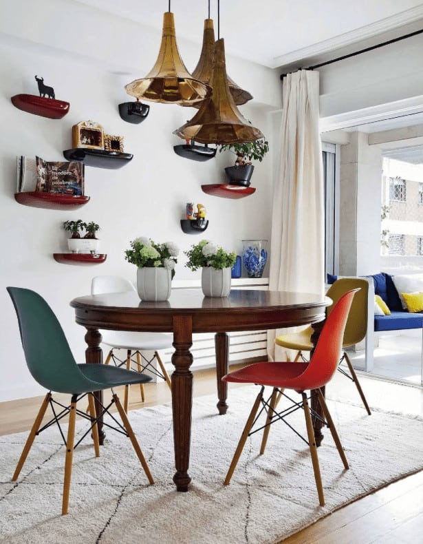 The white dining room showcases vintage pendant lights and high gloss floating shelves filled with various decors. It includes a wooden dining table and multi-colored modern chairs that sit on a beige rug.