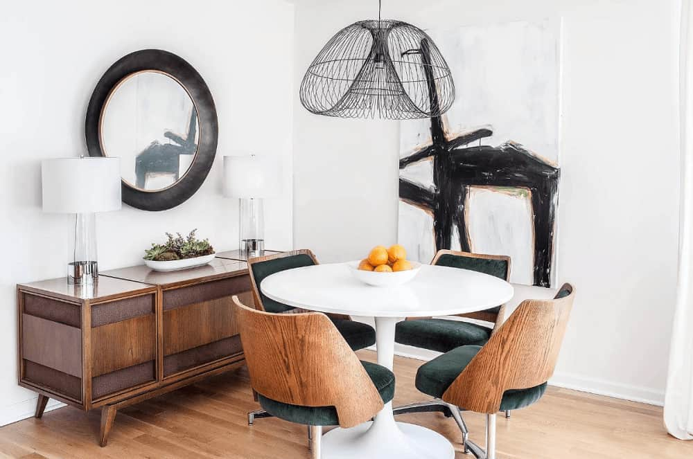 This dining room is designed with interesting artwork and a round mirror that hung above the wooden console table topped with glass table lamps. It has a round dining table and cushioned chairs over the light hardwood flooring.