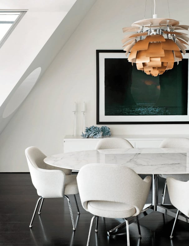 An eccentric chandelier illuminates this white dining room offering a marble top dining table and modern chairs over the dark hardwood flooring. It includes a large black framed wall art mounted above the sleek console table.