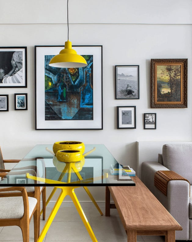 Small dining room designed with gallery frames that are mounted across the glass top dining table flanked by beige cushioned chairs and a wooden bench. It is lighted by a yellow dome pendant that complements the bowls and table's legs.