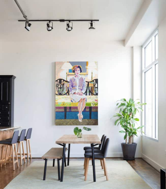 Small dining area decorated with a gorgeous painting that's mounted across the wooden dining set on a beige area rug. It has natural hardwood flooring and a large framed window allowing natural light in.