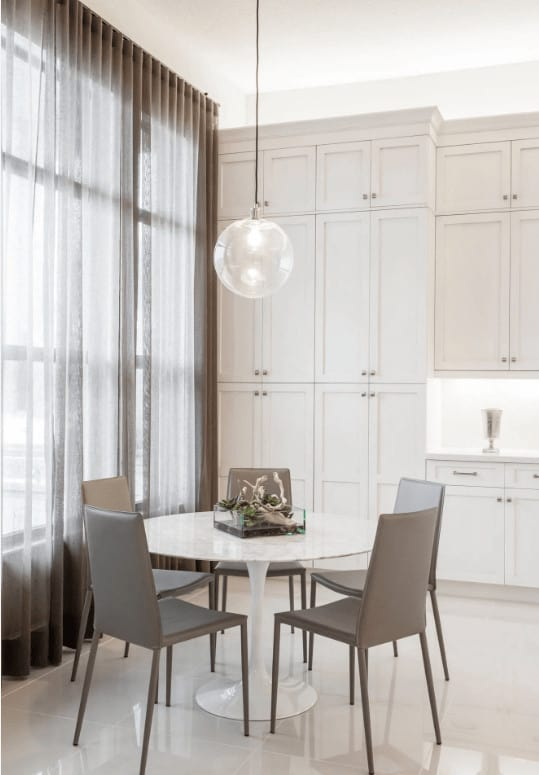 Sleek taupe chairs surround a marble dining table lighted by a glass globe pendant. This room has white tiled flooring and full height windows covered in sheer curtains.