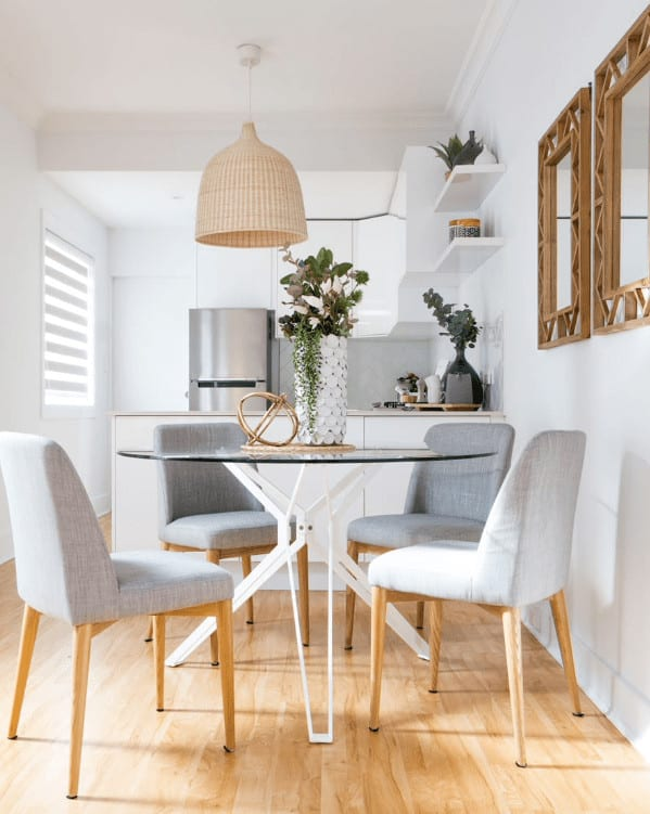 Small dining area with gray upholstered chairs and a round dining table topped with a gorgeous flower vase and spherical brass decor. It has light hardwood flooring and white walls mounted with a pair of wooden framed mirrors.