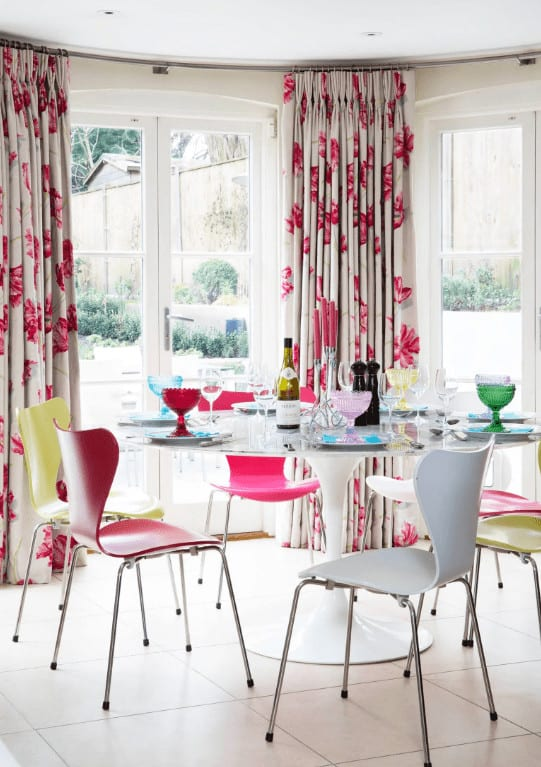Multi-colored chairs and floral draperies bring a pop of color in this airy dining room with tiled flooring and a French door leading out to the green yard enclosed in a wooden fence.