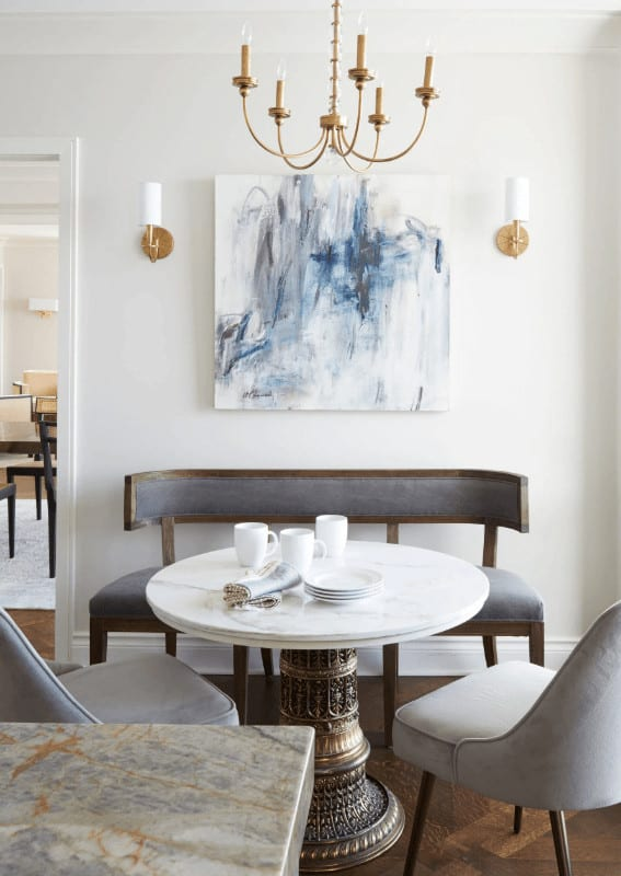 A cool abstract painting flanked by brass sconces hangs above the cushioned bench that's placed against the white wall. It is accompanied by a candle chandelier along with gray chairs and a marble top dining table with an intricate base.