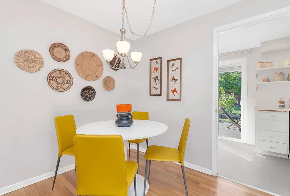 Sleek yellow chairs stand out in this dining room with a chrome chandelier and round dining table topped with a lovely vase. It is decorated with round wall arts and rectangular artworks mounted on the white walls.