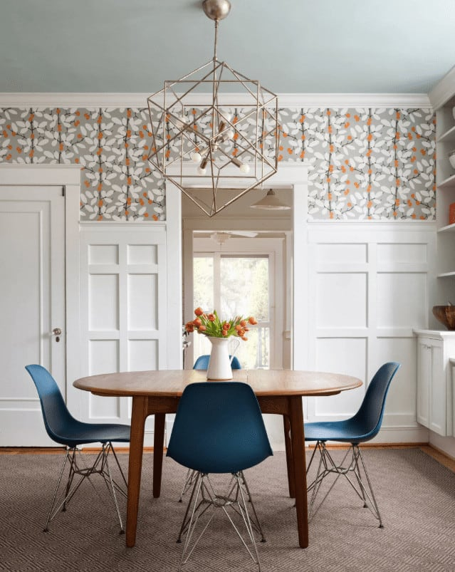 A geometric chandelier illuminates the wooden dining table surrounded by blue modern chairs over a brown area rug. This room is clad in floral wallpaper and white wainscoting.