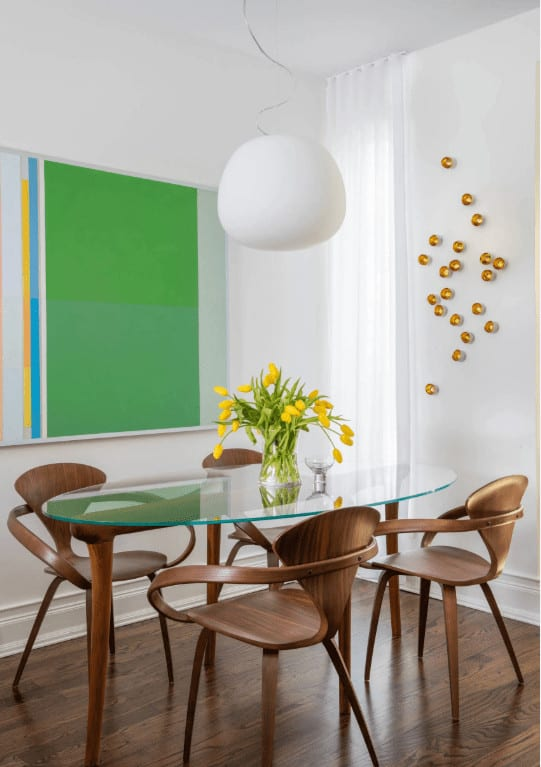 Green wall art adds a nice accent in this dining room featuring a glass top dining table and stylish wooden chairs that blend in with the hardwood flooring. It is illuminated by a sleek white chandelier that hung from the regular ceiling,