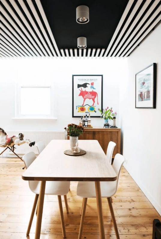 A black striped ceiling adds a striking contrast to the white walls mounted with framed artworks. This room boasts a sleek dining set and a wooden console table that complements the wide plank flooring.