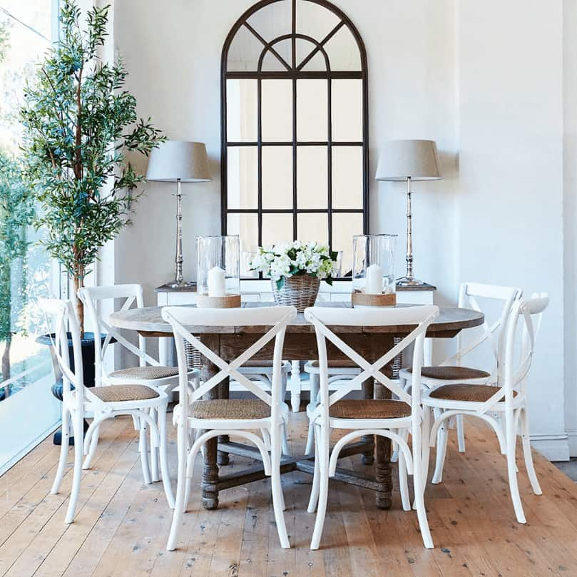 The traditional dining room showcases an oval dining table and white cushioned chairs over wide plank flooring. It includes a console table underneath an arched window that's framed in black aluminum.