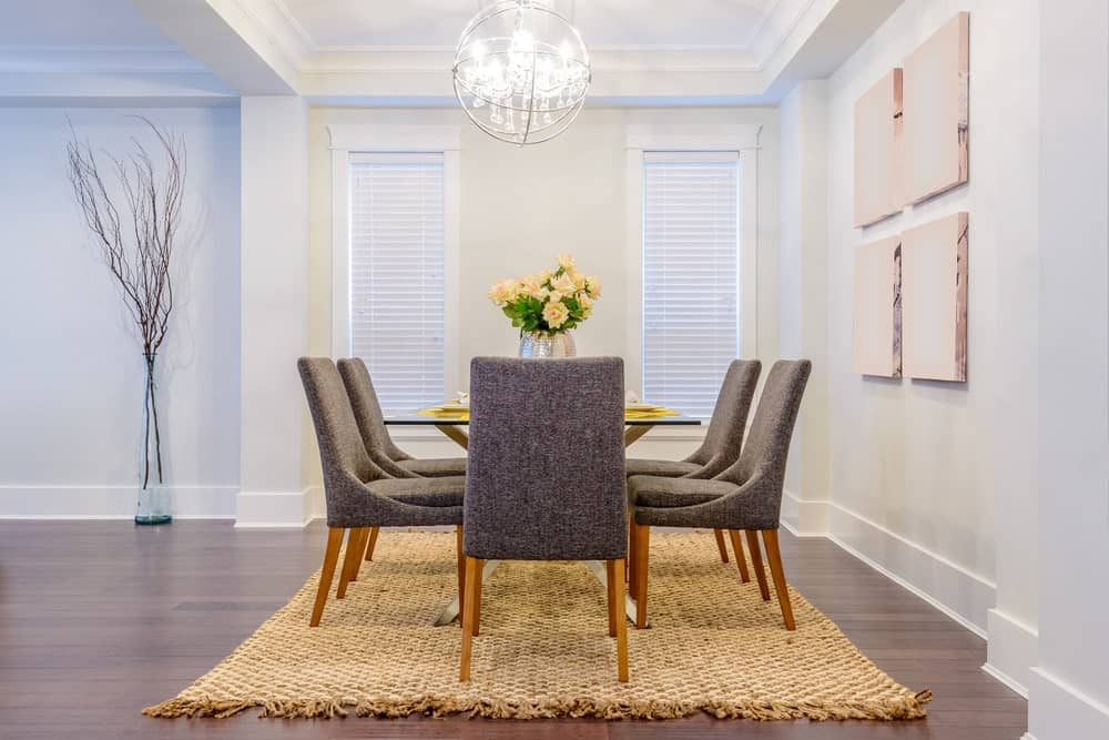 A spherical pendant light illuminates this dining room boasting gray cushioned chairs and a glass top dining table over a woven area rug. It has wide plank flooring and white walls mounted with gallery frames.