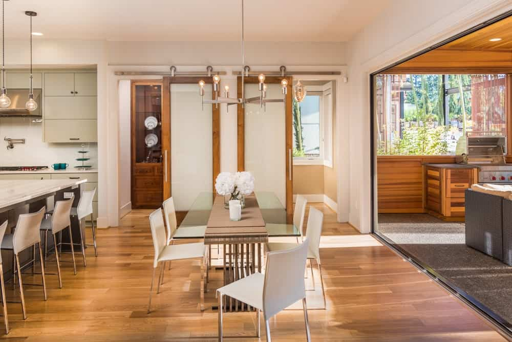 The warm dining area showcases sleek white chairs and a glass top dining table lined with a beige runner. It is illuminated by a modern chandelier that hung from the regular ceiling.