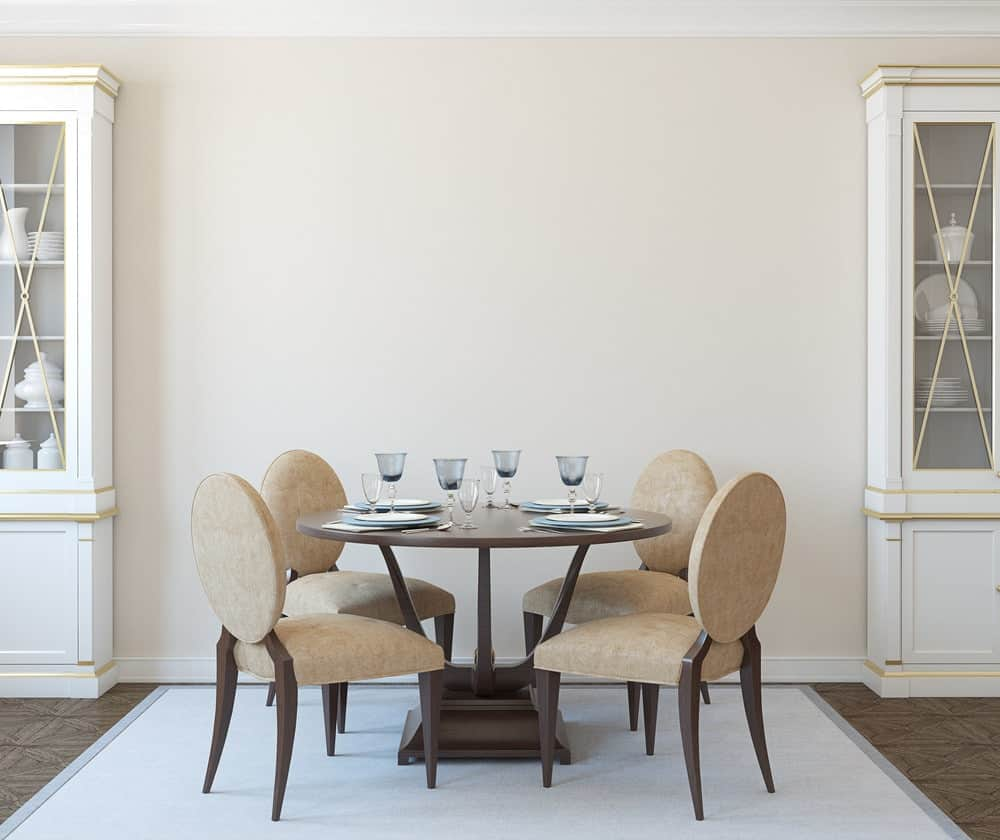 Beige round back chairs surround a wooden dining table that sits on a gray area rug over tiled flooring. It is flanked by white display cabinets that are lined with gold trims.