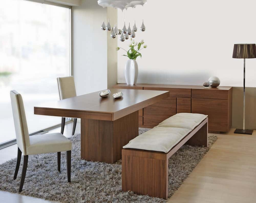 Beige upholstered chairs and a cushioned bench on a shaggy rug surround a sleek dining table under a unique pendant. It is accompanied by a floor lamp and a wooden buffet table topped with white vase and round decor.