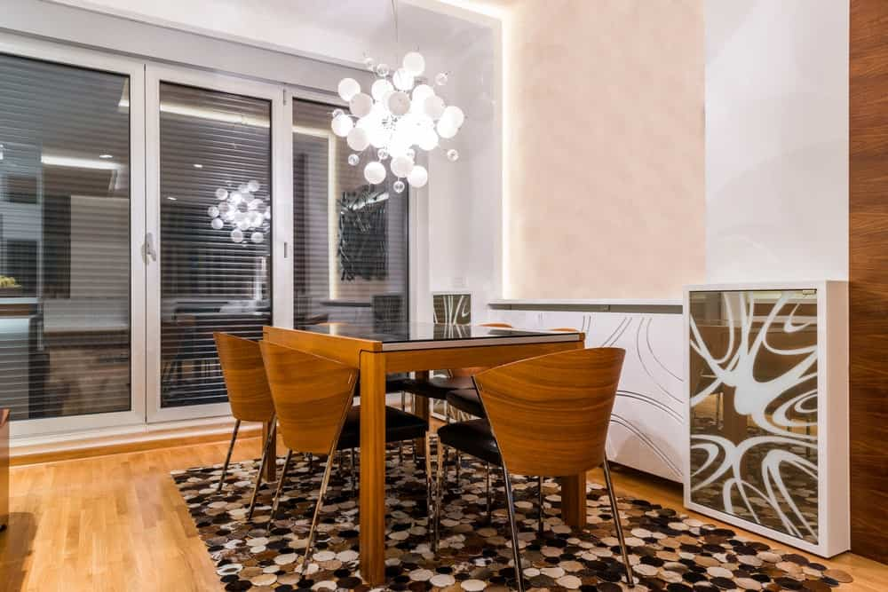 Fabulous dining room illuminated by a contemporary chandelier that hung over the wooden dining table surrounded by matching cushioned chairs. It has a stylish wall and rich hardwood flooring topped by an eye-catching area rug.